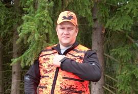 Riistanhoitoyhdistyksen toiminnanohjaaja Jarkko Nyströmin päällä olevat oranssit asusteet erottuvat mainiosti vihreitä kuusen havuja ja runkoja vasten.