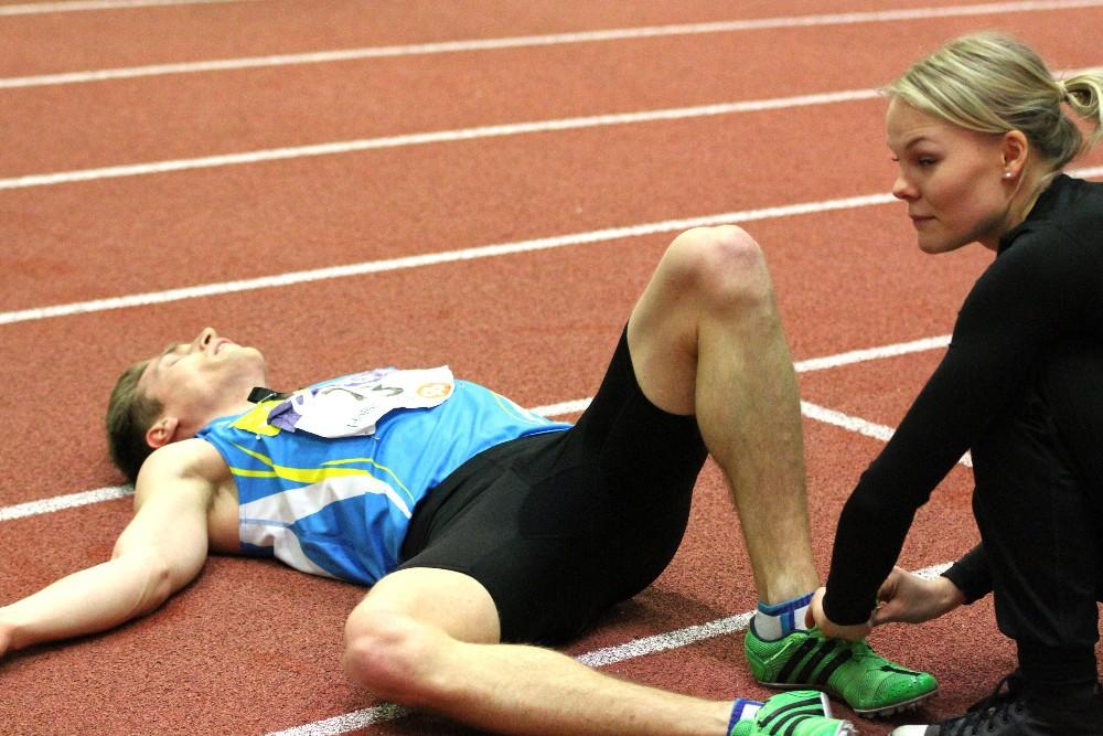 Eemeli Salomäki 7-ottelun viimeisen lajin 1000 metrin juoksun jälkeen kaikkensa antaneena. Puoliso Reetta Hämäläinen avaamassa piikkarinnauhoja.