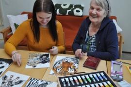Piirtäminen yhdistää lapsenlasta ja mammaa. Saattaa isoäiti joskus neuvoakin. Hely Lindroosin (oik.) luona maalausvälineet ovat aina esillä olohuoneen pöydällä. Manta Lindroos korjailee akryylitöitään.
