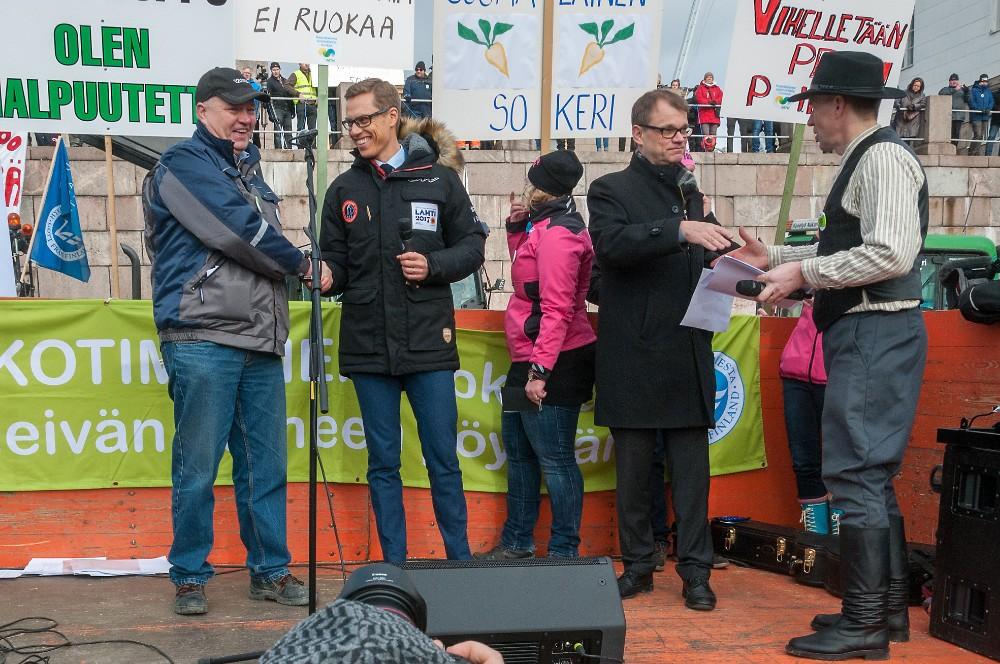 MTK:n puheenjohtaja Juha Marttila (oik.) ojensi valtioneuvostolle ja eduskuntaryhmille osoitetun vetoomuksen pääministeri Juha Sipilälle ja valtiovarainministeri Aleksander Stubbille. Kättelemässä myös SLC:n puheenjohtaja Holger Falck. Kuva Sauli Kaipainen.