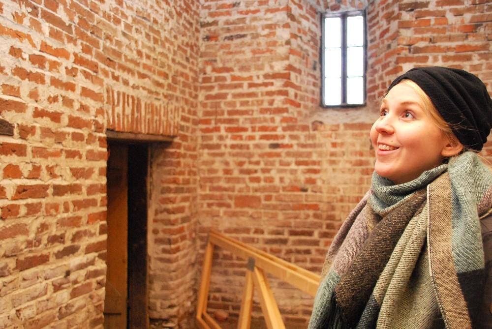 Kulttuurituottaja Miia Raivikko ihastelee kivimakasiinin sisäseinien tiiliä.