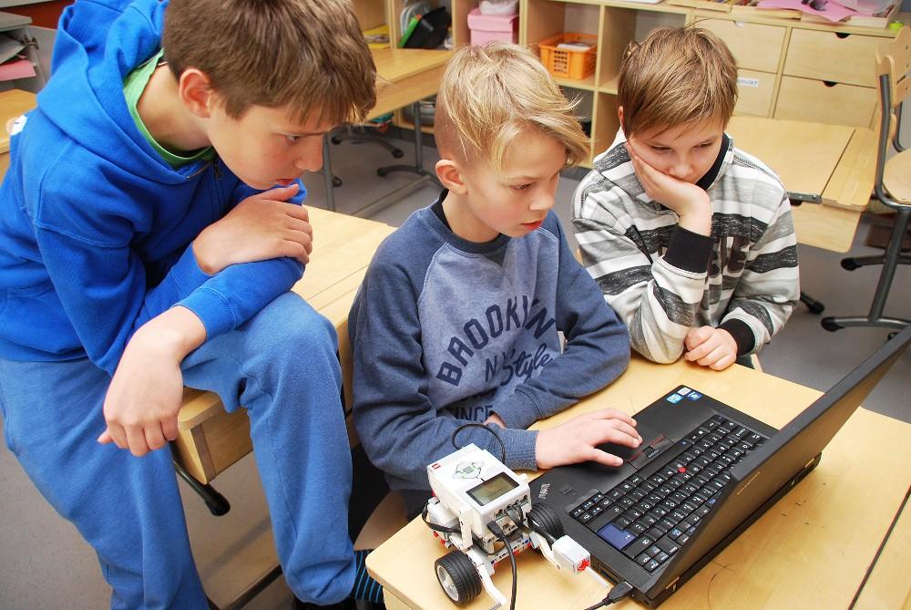 Markus Klemola opettaa nuorempiaan Juho Klinga ja Aleksi Vesantoa ohjelmoimaan Lego-robottia.